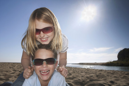 Girl and boy with sunglasses at beach