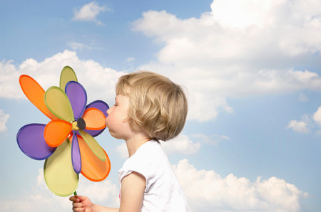 young girl blowing toy windmill