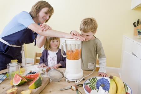 boy, girl and mum making fruit smoothies 免版税图像 - 114156299