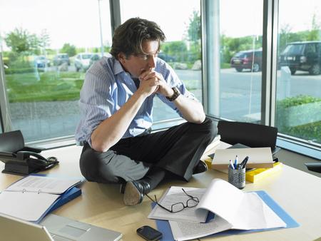 Man sitting on his desk, thinking