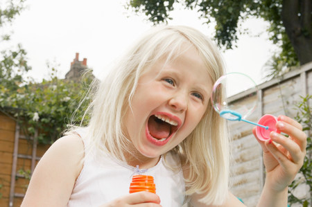 young girl having fun blowing bubbles
