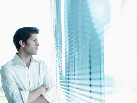 Business man looking through window Imagens