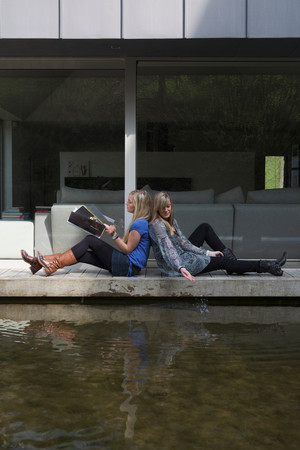 teenages reading a magazine near water Reklamní fotografie