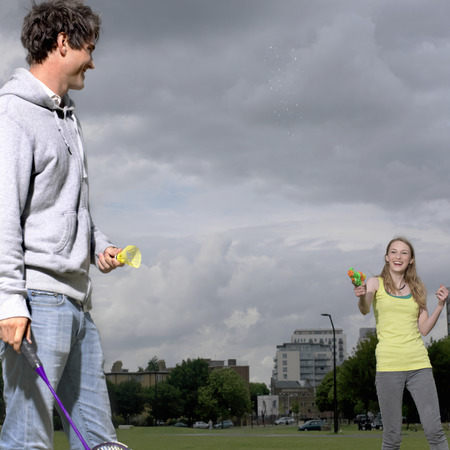 Young couple shooting water pistol Banque d'images - 114076835