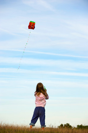 Girl flying a kite in a field 写真素材