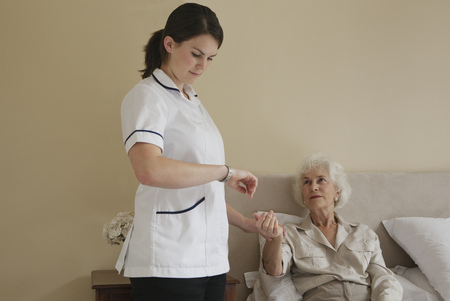 Nurse taking pulse of elderly woman