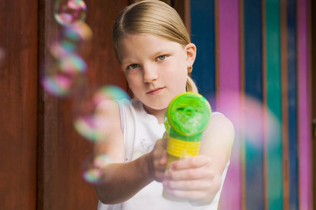 girl pointing bubble gun to camera