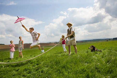 Happy people jump roping in countryside