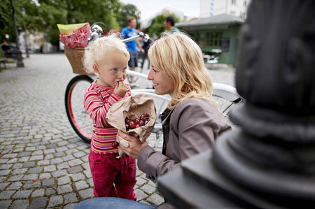 Little girl and mother eating cherries Banque d'images - 113926504