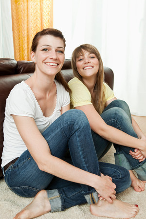 Two young women sitting on the floor