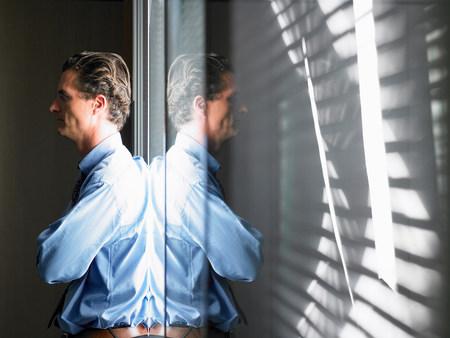 Man against window, thinking Imagens