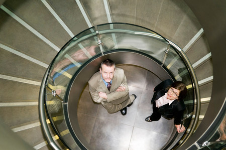Business couple in a spiral stairwell