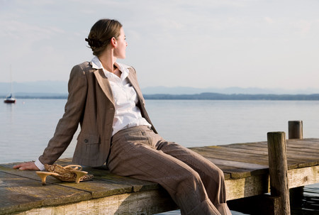 woman sitting on pier at lake