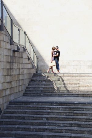 couple kissing on top of stairs