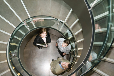 Business trio in a spiral stairwell