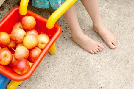 girls feet next to apples in wheelbarrow