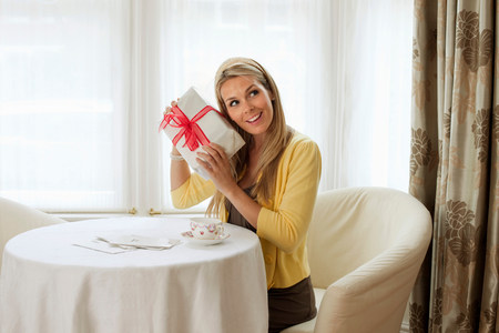 Attractive young blond woman with gift