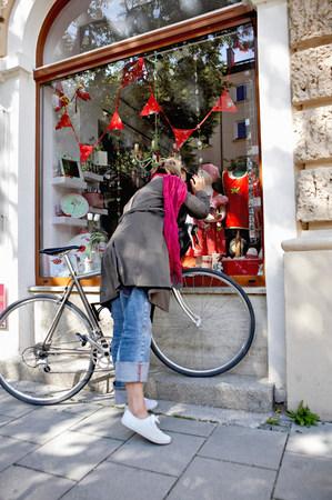Woman with bike looking into window