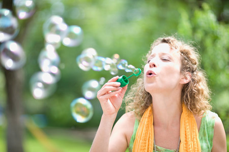 young woman blowing bubbles 스톡 콘텐츠
