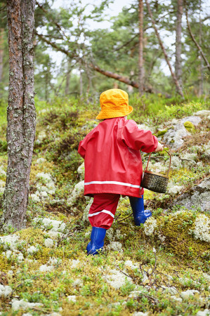 Toddler with basket walking in forest