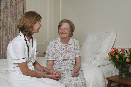 Nurse holding elderly womans hand