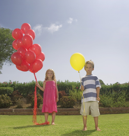 Young children holding red balloons Stockfoto