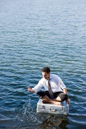 businessman sitting on floating suitcase Imagens