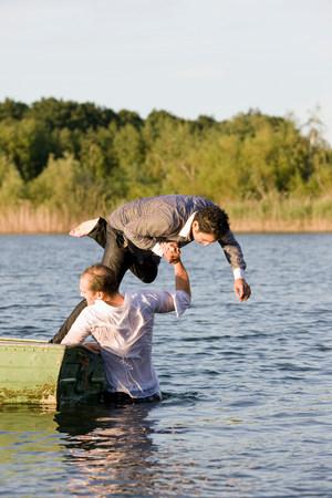 businessman throwing friend in water