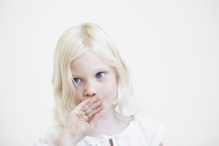 Young girl with hand up to mouth Stock Photo