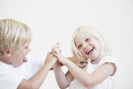 Young boy tickling young girl Stock Photo