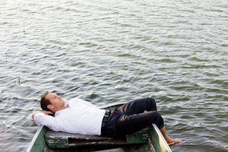 businessman relaxing in rowboat Stock Photo