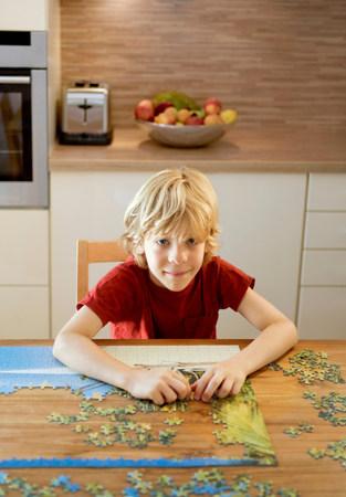 Portrait of a boy doing a puzzle Imagens
