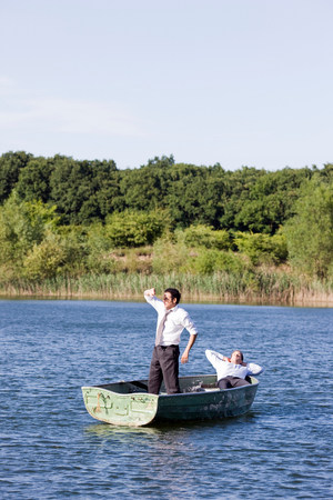 two businessmen relaxing in rowboat