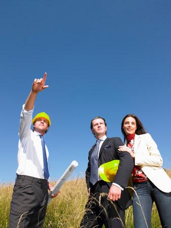 contractors with blueprints in field