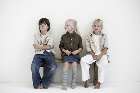 Portrait of two boys and a girl on bench Stockfoto