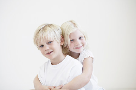 Portrait young girl hugging young boy