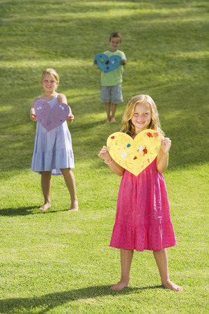 Young children holding paper hearts Stockfoto