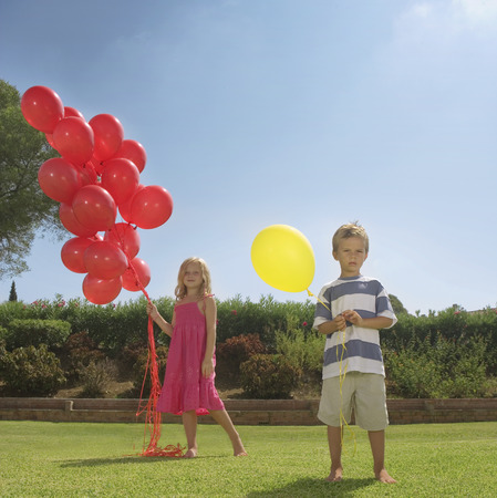 Young children holding red balloons Фото со стока