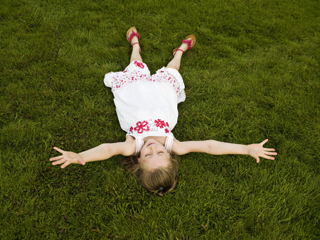 Girl lying arms outstretched on a lawn