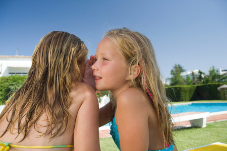 Two young girls sharing a secret by pool Banque d'images - 114047211