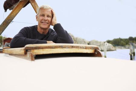 Middle aged man on old boat Banco de Imagens - 114014294