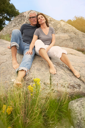 Middle aged couple, cuddling on rocks Banco de Imagens - 113895749