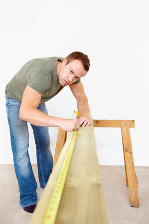 Man measuring wooden plank Stock Photo