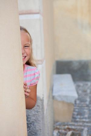 girl hiding behind wall, laughing