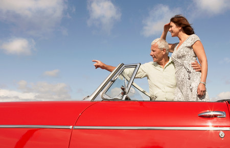 Senior couple in sports car, pointing Banco de Imagens