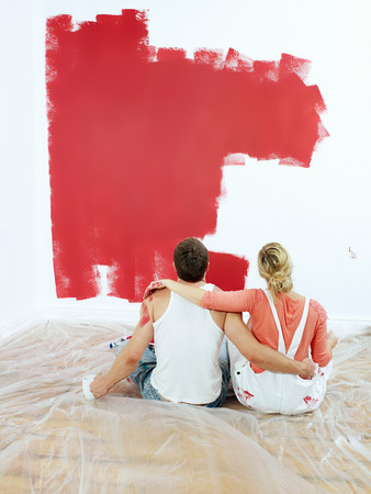 Couple contemplating painted wall Stock Photo