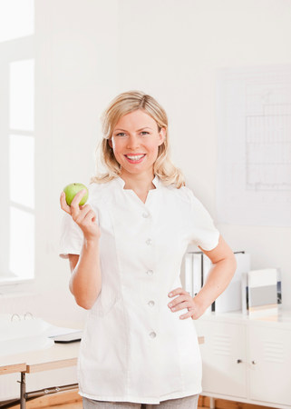 Woman in a white lab coat with an apple