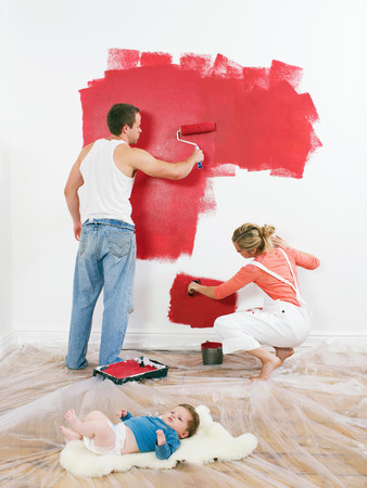 Couple painting a wall, baby on floor Stock Photo
