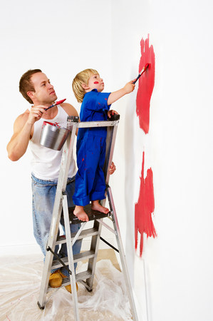 Man and toddler boy painting wall red Banque d'images - 114047326