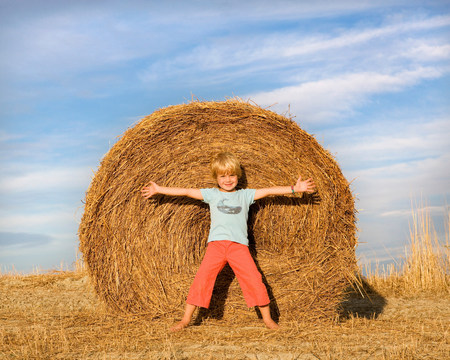 boy standing in front of hay bale